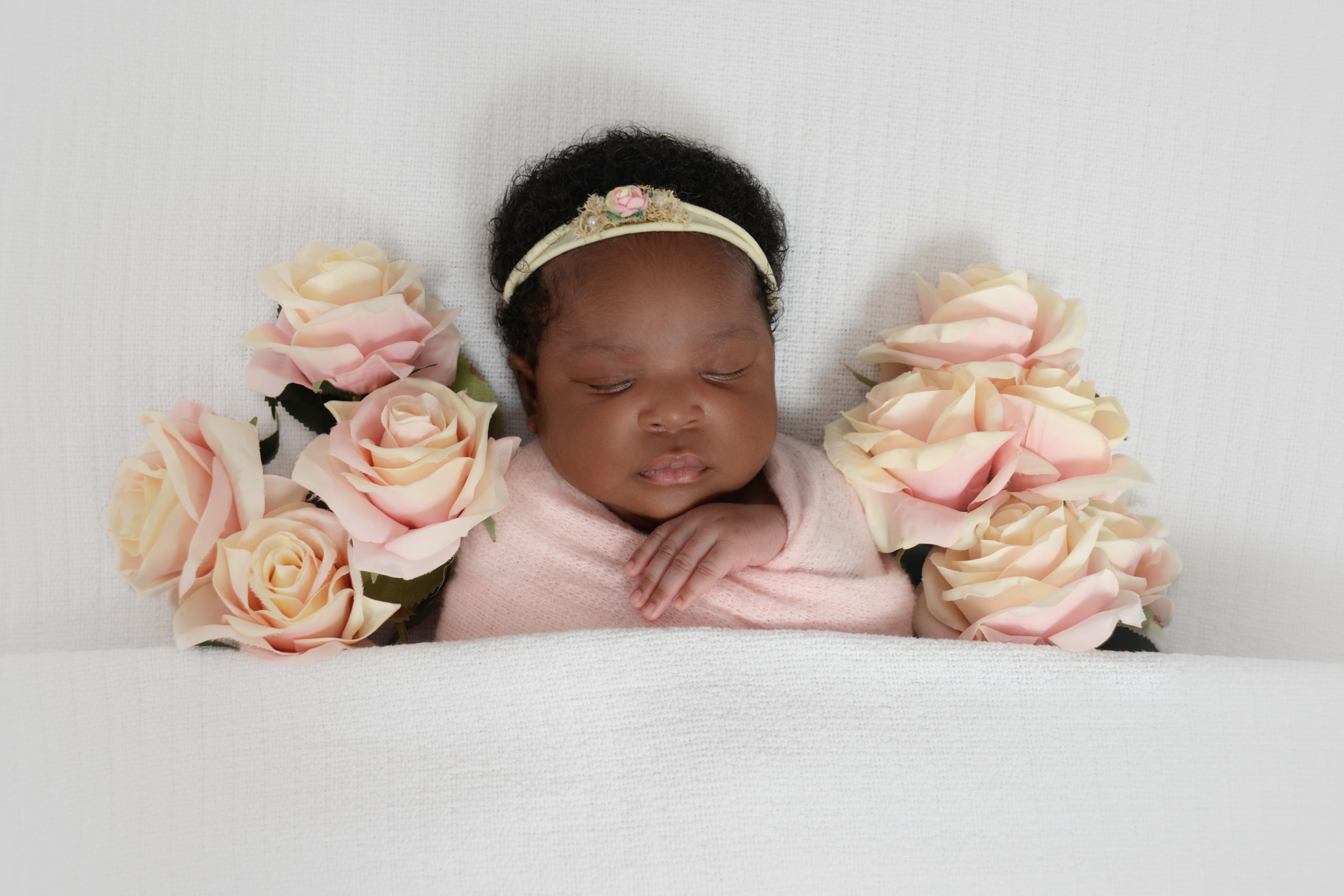 Newborn baby girl with roses by Thanet Newborn Photographer